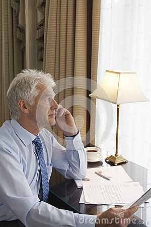 Free Middle Aged Businessman On Call At Desk Stock Photography - 33846182