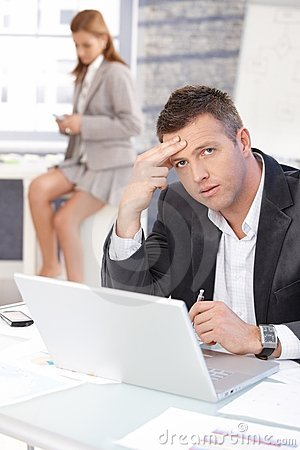 Middle-aged businessman sitting troubled at desk