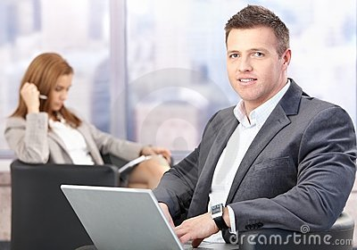 Middle-aged businessman using laptop in hall
