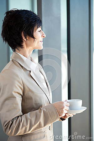 Middle aged businesswoman drinking coffee