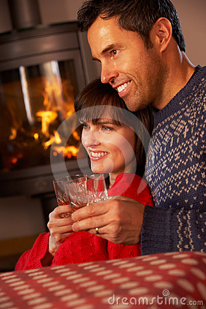 Middle Aged Couple By Cosy Log Fire With Drinks