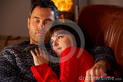 Middle Aged Couple Cuddling By Cosy Log Fire