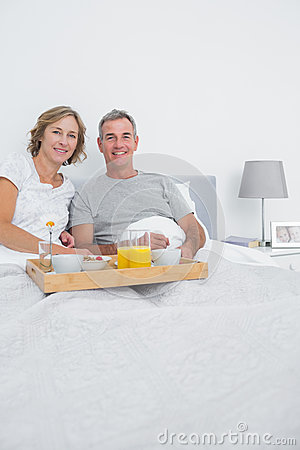 Middle aged couple having breakfast in bed together