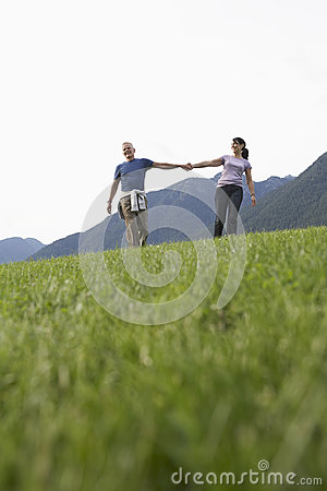 Middle Aged Couple Holding Hands On Meadow