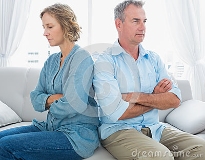 Middle aged couple sitting on the couch not speaking after a fig