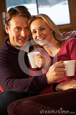 Free Middle Aged Couple Sitting On Sofa With Hot Drinks Stock Images - 25640224