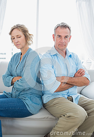 Middle aged couple sitting on the sofa not speaking after a disp