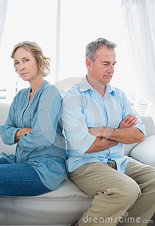 Middle aged couple sitting on the sofa not speaking after a figh