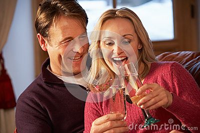 Middle Aged Couple On Sofa With Champagne