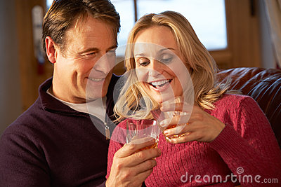 Middle Aged Couple On Sofa With Glasses Of Whisky