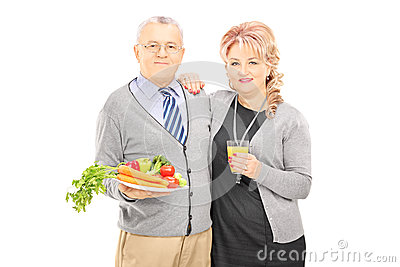 Middle aged couple standing close together holding a healthy foo