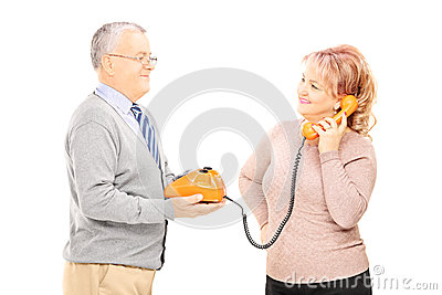 Middle aged couple using old telephone