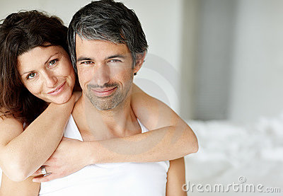 Middle aged happy couple relaxing in bedroom