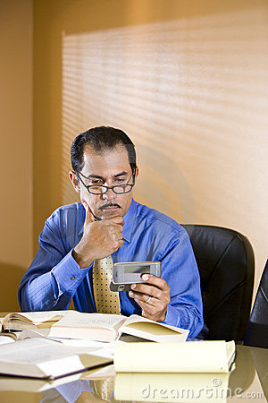 Middle-aged Hispanic businessman texting