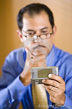 Middle-aged Hispanic businessman texting