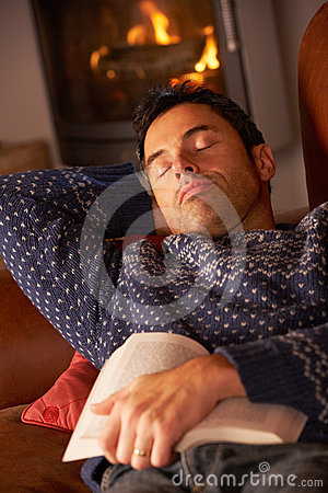 Middle Aged Man Asleep With Book By Cosy Log Fire