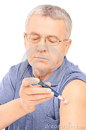 Middle aged man injecting insulin in his arm