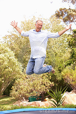 Middle Aged Man Jumping On Trampoline In Garden