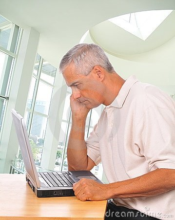 Middle aged Man Looking Intently at Laptop