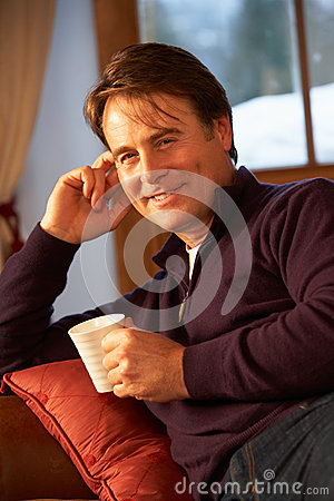 Middle Aged Man Relaxing With Hot Drink On Sofa