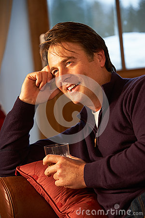 Middle Aged Man Relaxing On Sofa Drinking Whisky