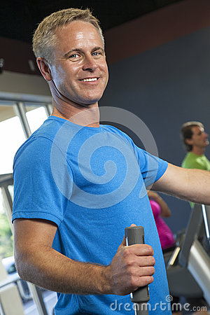 Middle Aged Man Running on Gym Exercise Machine