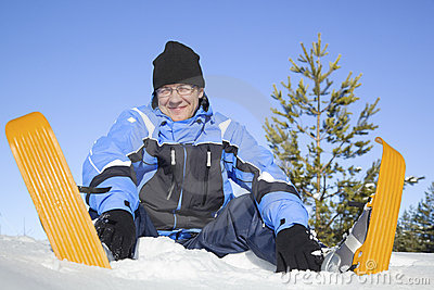 Middle-aged man sitting in snow