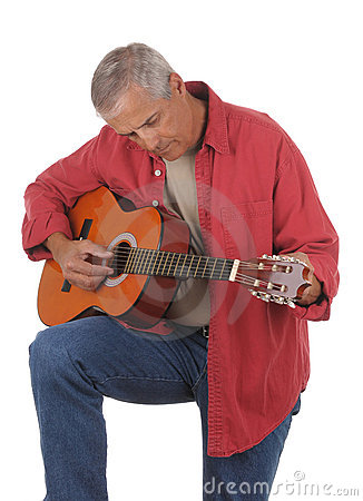 Middle aged man tuning guitar