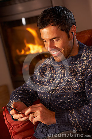 Middle Aged Man Using MP3 Player By Cosy Log Fire
