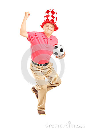 Middle aged sport fan with hat holding a ball and gesturing happ