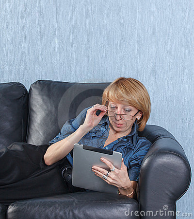 Middle aged woman using tablet PC on couch