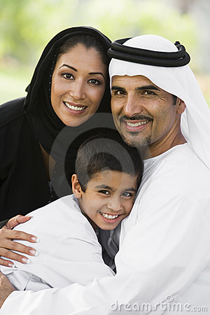 A Middle Eastern couple and their son in a park