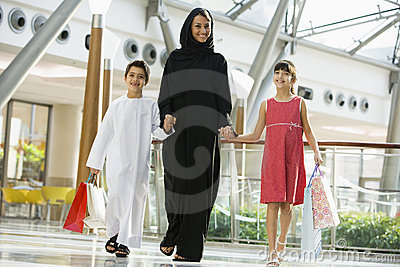 A Middle Eastern woman with two children shopping