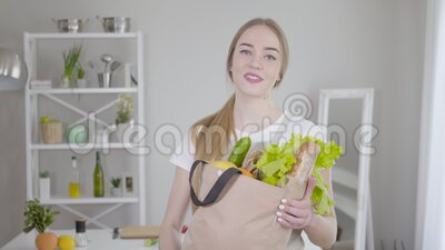 Middle shot of young pretty girl posing with grocery bag at home. Blond Caucasian woman holding healthy delicious. Products and smiling at camera. Lifestyle stock footage