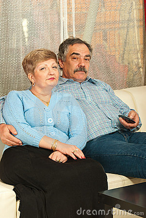 Middleaged couple watching tv home