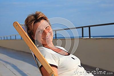 Middleaged woman in lounge on veranda over sea