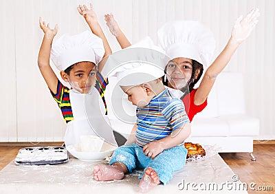 Miúdos em trajes do cozinheiro