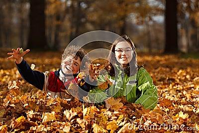 Miúdos que jogam no parque do outono