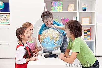 Miúdos que olham o globo da terra