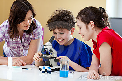 Miúdos que usam o microscópio