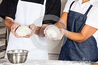 Chefs Presenting Dough In Kitchen