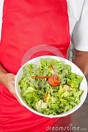 Cocinero que presenta la ensalada