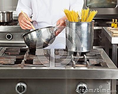 Cocinero que cocina los espaguetis