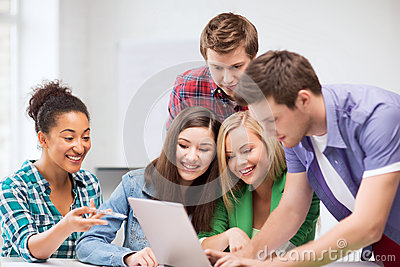 Międzynarodowi ucznie patrzeje laptop przy szkołą