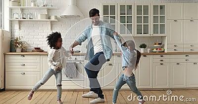 Mieszany ojciec wyścigu i dzieci tańczące razem w nowoczesnej kuchni zbiory