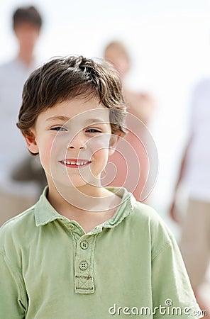 Miling little boy standing outside