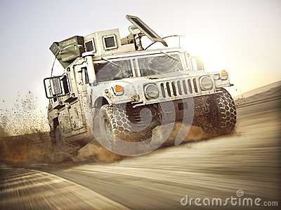 Military armored vehicle moving at a high rate of speed with motion blur over sand. Generic Stock Photo