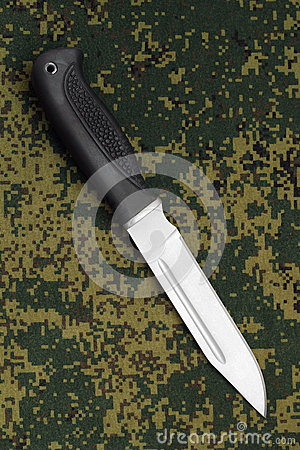 Military knife lying diagonally on camouflage background