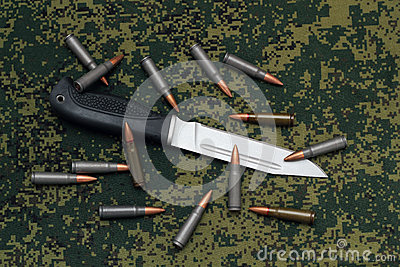 Military sheathless knife and cartridges on camouflage backround