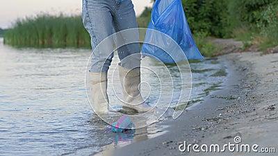 Miljö- problem, den unga aktivistflickan in i gummistöveler gör ren strand från plast- rackar ner på och samlar stock video